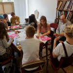 A group of young people are sat around a large table writing together