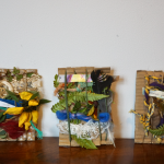 Three pieces of art are standing on a table, they are made from textiles and natural found objects