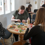 A group of women are sat around tables creating small pieces of art from textiles and found objects