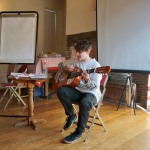 A young performer is sat down playing guitar and singing