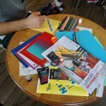 A man is sat at a table creating a zine from coloured paper, newspapers and pens
