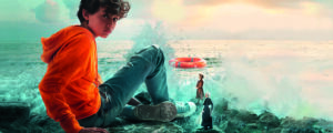 The cover of Boy Giant, a book by Michael Morpurgo. The image features a young boy stting in front of a sea
